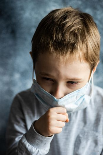 COVID-19 virus concept with boy in face mask sneezing