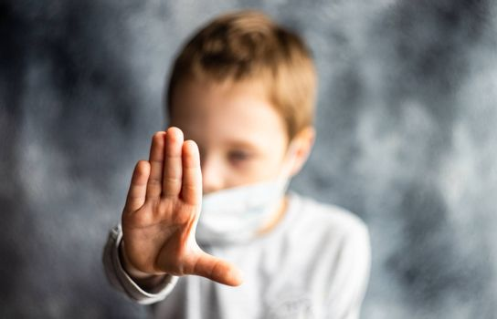 COVID-19 virus concept with boy in face mask showing with hand to stop