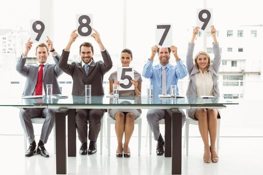 Interview panel holding score cards in office