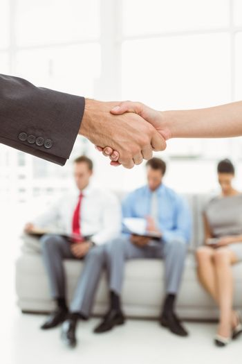 Handshake besides people waiting for job interview in office