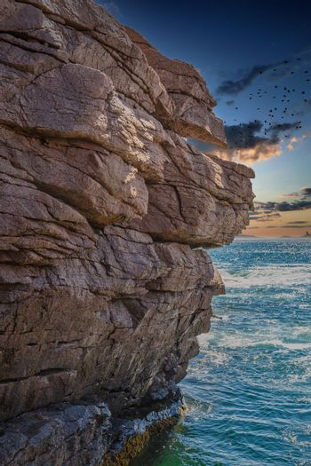 Rocky Cliffs Over Blue Sea at Sunset