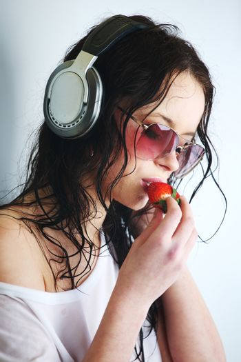 Young woman listening to music on headphones eating strawberry. Closeup portrait of girl on light background with copy space