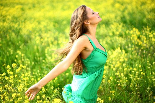 Young woman enjoy life dancing on oilseed flower field