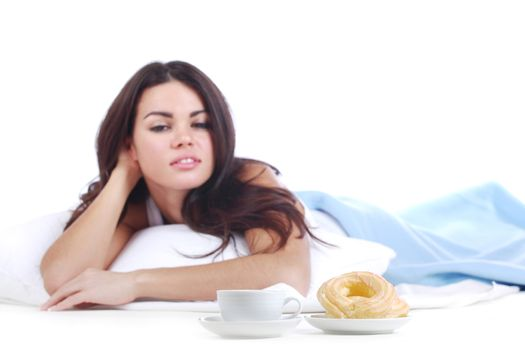 Woman eating a donut and drink coffee in the bed isolated on white background