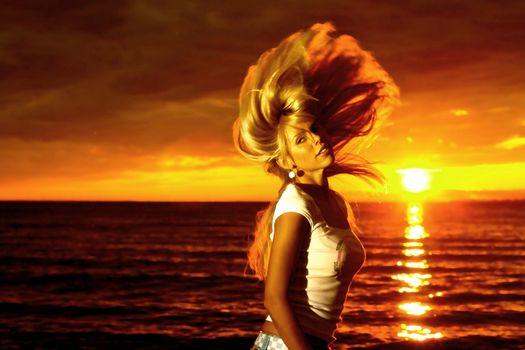 Beautiful girl hair waving motion on golden sunset over sea