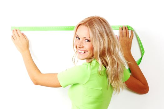 Young beautiful smiling woman measuring spacing on a wall with green measure tape, white background