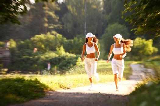 Two female runners run in summer park, women friends