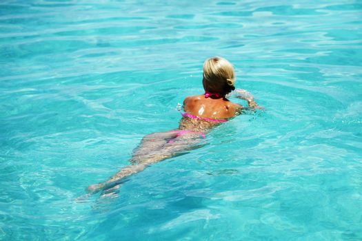 Beautiful woman swim in blue water of sea or swimming pool