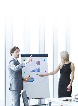 Businessman making financial presentation on flipchart at business meeting