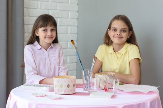 Children sit at the table and prepare for the celebration of Easter