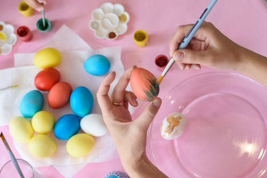 Hand paints a chicken egg on Easter