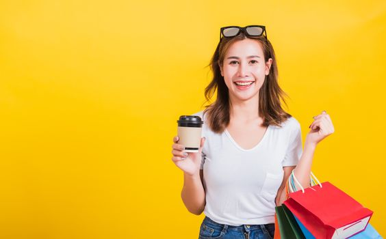 woman smiling hold shopping bags multi-color and take away coffe