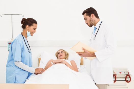 Doctors visiting patient in hospital