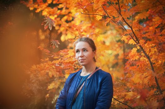 Woman autumn portrait in warm sunny october day with natural light.