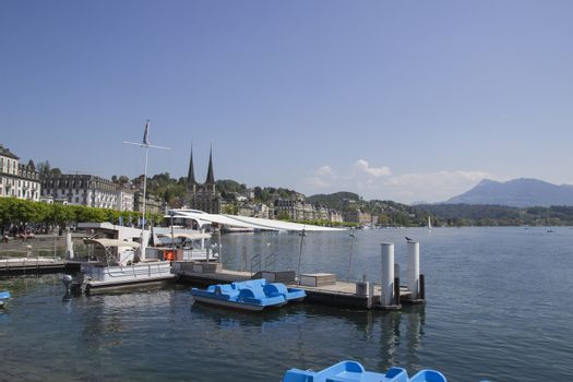 Emptie docks of Lake Lucerne under blue sky and majestic mountains.