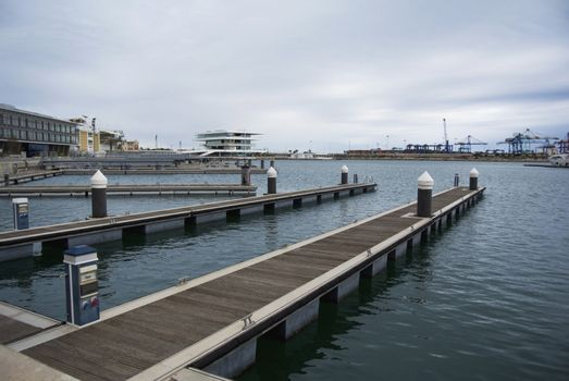 Empty docks in Valencia port, Spain. Valencia Port At Mediterranean Sea. Reflexion in the water. Empty docks in the Spanish port of Valencia in the beginning of spring. Cloudy sky.