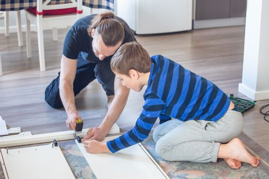 Family relations, fatherhood, parenting, hobby, carpentry, woodwork concept - Father and son making constructing furniture together at home