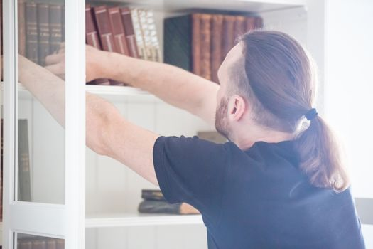people, knowledge, education and school concept - close up of man taking book from shelf in domestic library