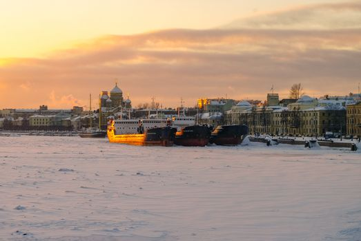 St. Petersburg, Russia - January 26, 2011:  Winter sunset view of the Big Neva and the embankment of Lieutenant Schmidt from the Annunciation (Blagoveshchensky) bridge with ships, St. Petersburg, Russia