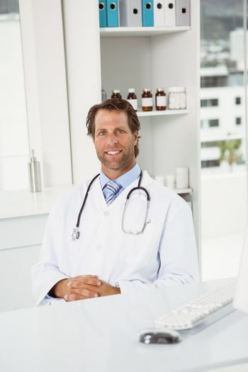 Smiling doctor sitting in medical office
