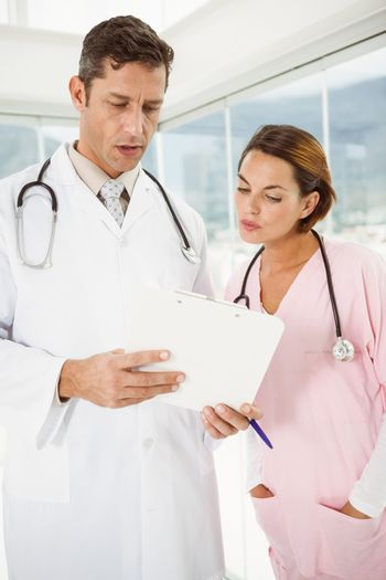 Doctors discussing reports at medical office