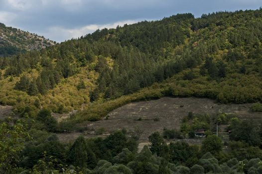 Amazing autumn view of glade, field, peak, deciduous forest, trees and small village in Sredna gora mountain, Bulgaria