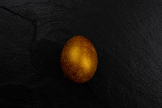 One big golden easter egg on dark black stone background copy space for text