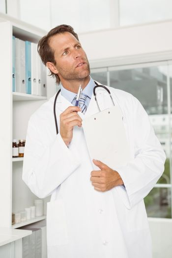 Thoughtful doctor with reports at medical office