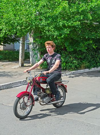 Full-length portrait a male student moves on a motorbike.