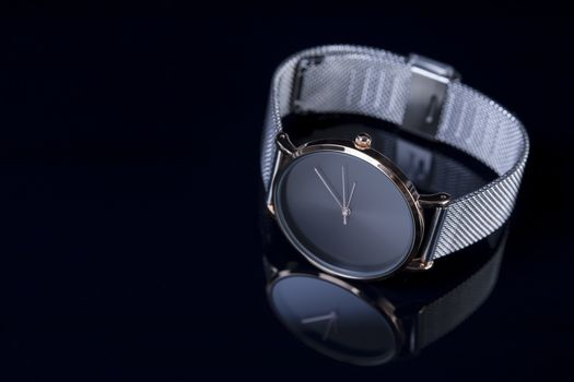 Black wrist watch for women with metal bracelet on glossy black background. Focus on the key of the watch