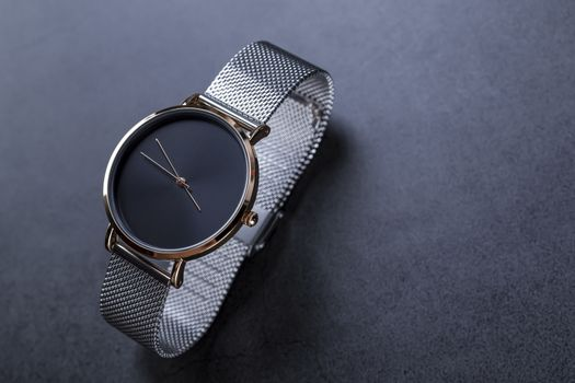 Black wrist watch for women with metal bracelet on black background.