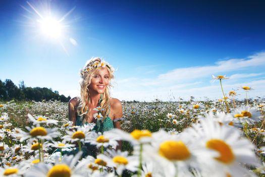 Beautiful girl in dress on the sunny daisy flowers field