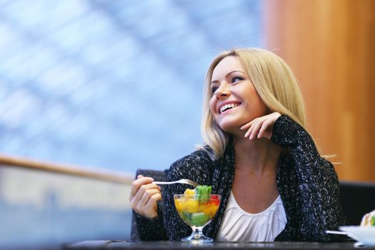 Happy smiling woman eat fruit dessert in cafe