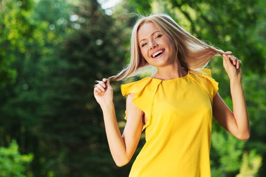 happy woman in yellow dress posing against a background of trees