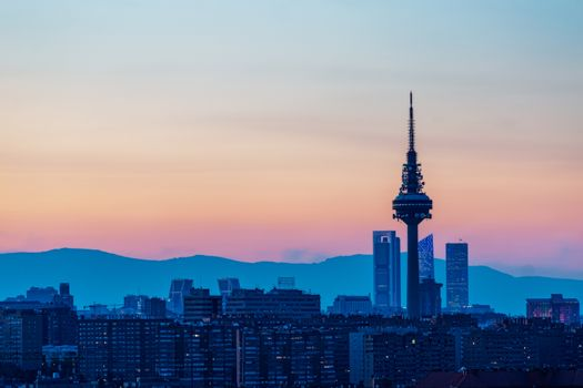 View of the skyline of Madrid, with the mountains in the background, in a beautiful sunset. Spain. City and travel concept.
