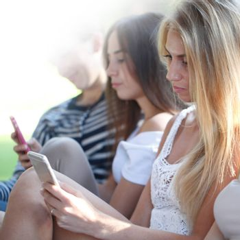 Portrait of young girls chatting with their smartphones outdoors