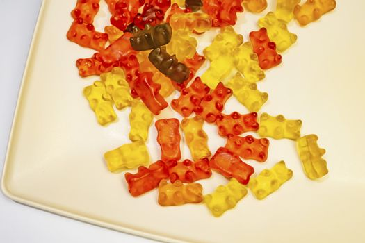 teddy bear figured and colorful jelly beans in plate on white background.