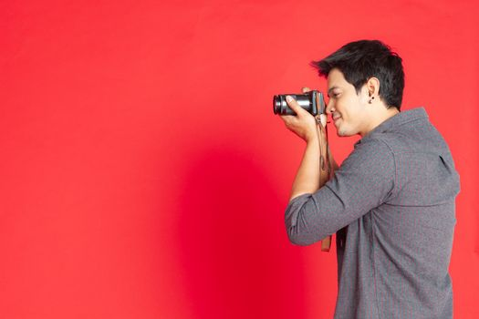 Young Asian hipster man searching for an interesting subject on the studio on a red background.Travel Lifestyle concept