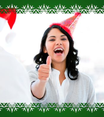 Positive businesswoman doing a thumbup to celebrate christmas
