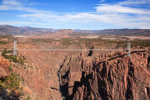 The Arkansas River Runs Through The Royal Gorge in Southern Colorado. Depicted here, the Royal Gorge suspension bridge spanning the large cleft in the earth with the Arkansas river carving the ancient gorge below it.