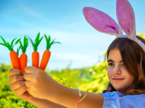 Portrait of a sweet little girl dressed as bunny playing with carrots, gardening and having fun outdoors in sunny spring day, Easter celebration outdoors