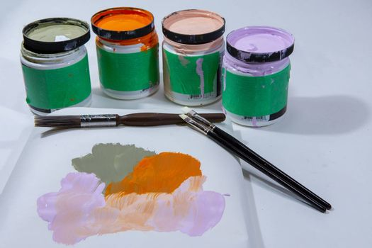Small cans of paints and brushes on a small piece of white paper for sample color selection
