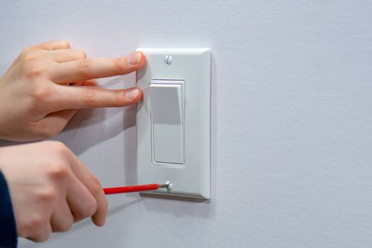 Attaching a white platband to an electric wall switch