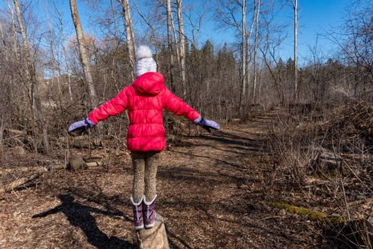 A girl in a spring forest stands on a stump and is about to jump down a path