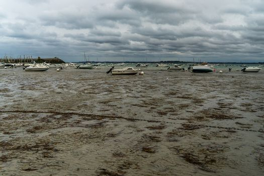 Sea and yachts during tide on sea shore of France in summer
