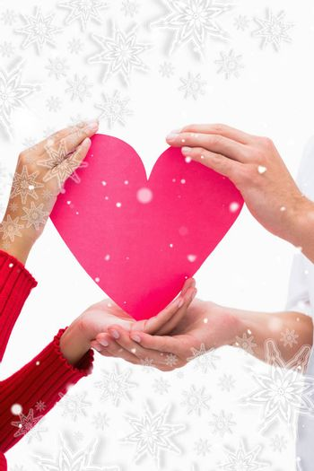 Couples hands holding pink heart against snowflakes