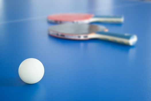 White ping-pong ball with rackets on background