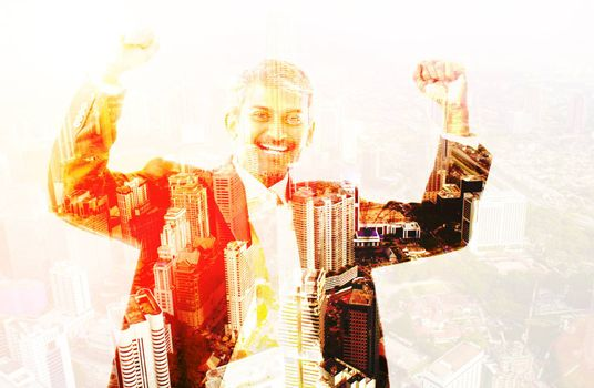 Double exposure image of excited business man celebrating success overlay with cityscape.
