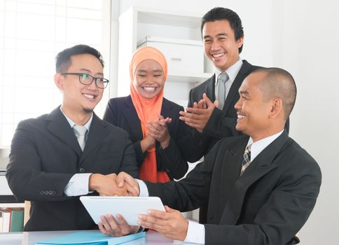 Group of Malaysian businesspeople having deals on desk inside office room, businesspeople clapping hands.