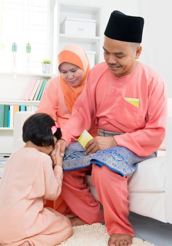 Asian Muslim Malay girl greeting to her father at home during hari raya. Malaysian people living lifestyle.